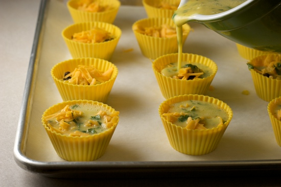 Next, whisk the eggs, sour cream, herbs and spices together in a bowl with a pour spout. Then carefully fill each muffin cup with the egg mixture.
