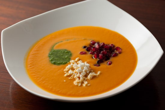 Spicy Pumpkin Soup with Cilantro Pepita Pesto, Pomegranate Arils, and Cotija Cheese