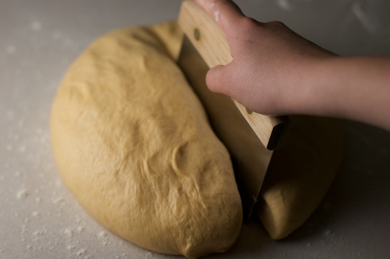 Cut the deflated dough in half with a knife or bench scraper.