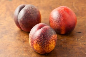 Ripe Nectarines sitting on a board