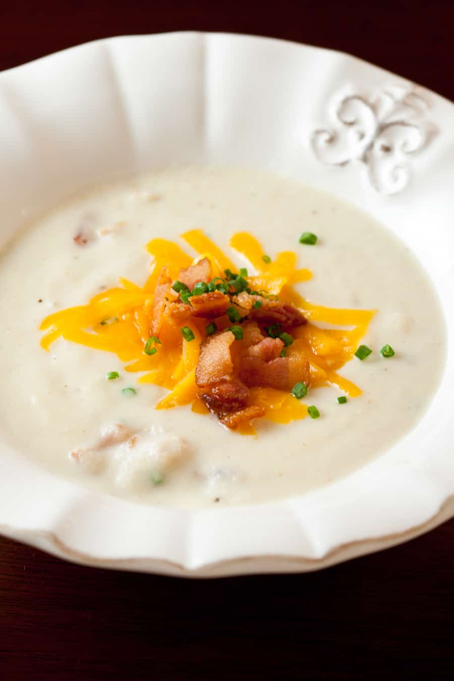 Loaded Cream of Cauliflower Soup with bacon, cheddar, and chives garnish in a white bowl.