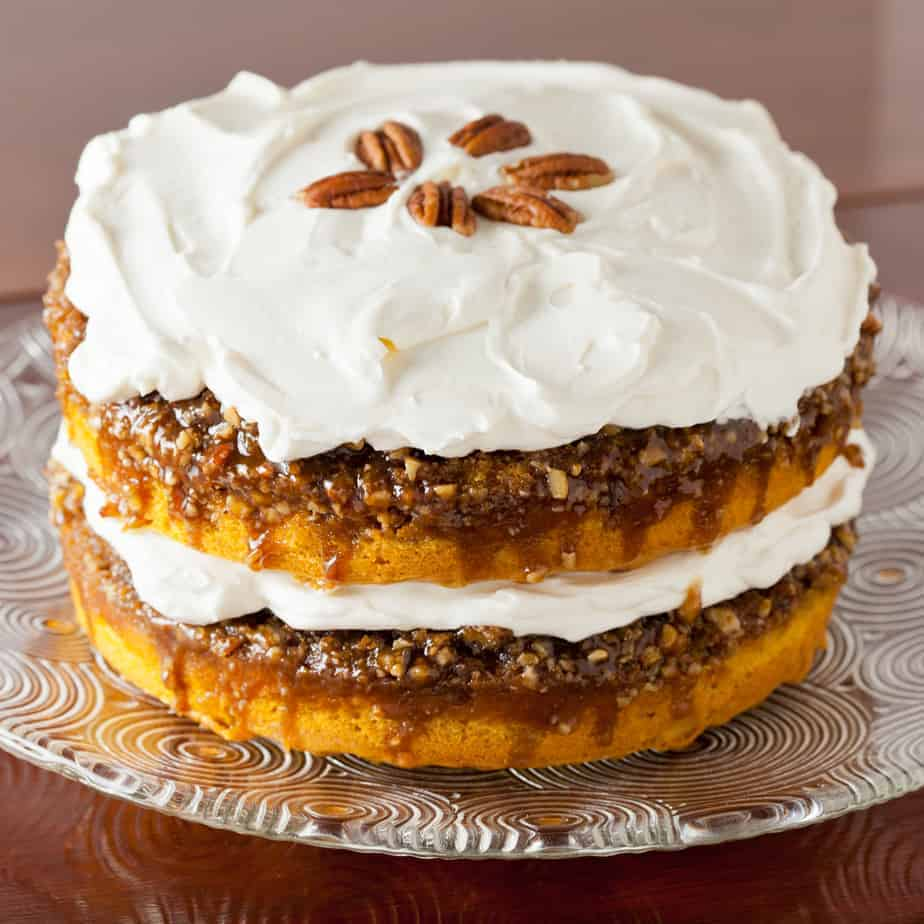Pumpkin Praline Cake with Whipped Cream Frosting garnished with pecans