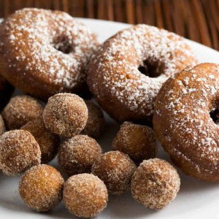 Pumpkin Spice Doughnuts dusted with powdered sugar on a plate