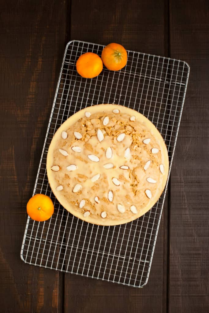 Citrus almond olive oil cake on cooling rack, glazed with citrus olive oil glaze and topped with sliced almonds